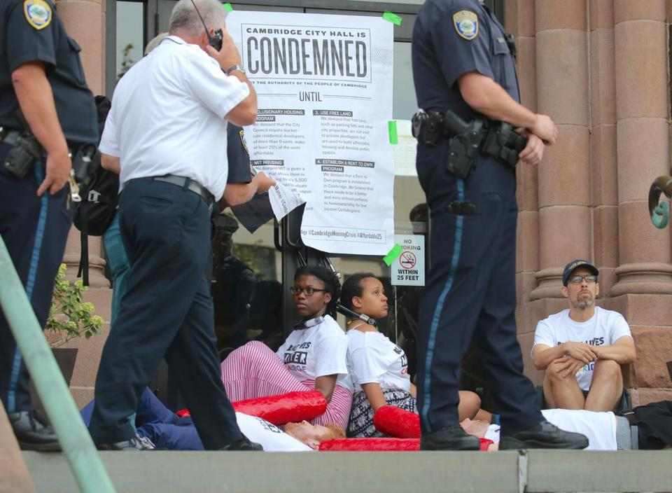 Protesters used bicycle locks and chains to block the front entrance of Cambridge City Hall Wednesday morning.